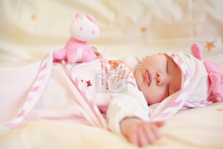 Photo for Lying sleeping baby with small teddy bear on bright background - Royalty Free Image