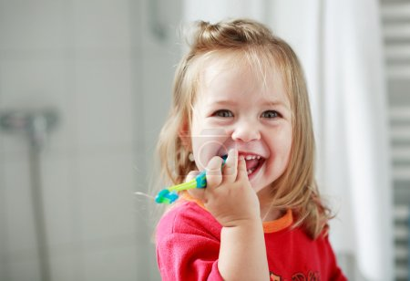 Small girl washing her teeth