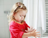 Small girl washing her hands