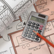 Red pencil and pocket calculator on house construc...