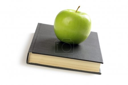 Green apple on book