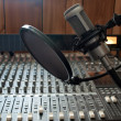 A studio vocal microphone over a mixing board cons...