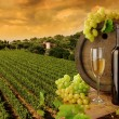 Wine barrel, bottle and glass with fresh grapes, on background of sunset vineyard