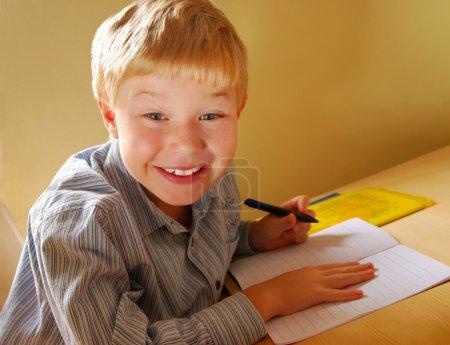 Photo pour Garçon mignon souriant, gaucher, faire ses devoirs - image libre de droit