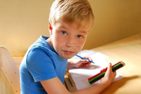 Photo pour Garçon mignon, gaucher, dessin aux crayons de couleur - image libre de droit