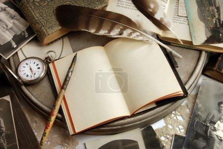 Foto de Composición de objetos de recuerdos familiares con cuaderno, pluma, libros y reloj de bolsillo. - Imagen libre de derechos
