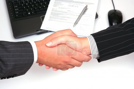 Photo for Man and woman shaking hands in front of laptop and signed contract - Royalty Free Image