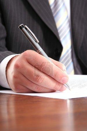 Photo pour Homme d'affaires écrivant sur un formulaire, gros plan - image libre de droit