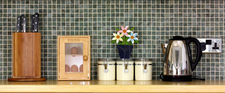 Photo for Tidy kitchen worktop with flowers against a tiled background - Royalty Free Image