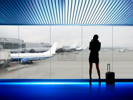 Photo pour Silhouette de femme d'affaires qui attend un vol à bord de l'avion à l'aéroport - image libre de droit