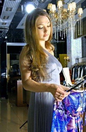 Photo pour Belle femme riche choisit une robe dans une boutique - image libre de droit