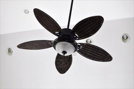 Foto de Ventilador de techo tropical marrón contra las paredes blancas con luminarias empotradas - Imagen libre de derechos