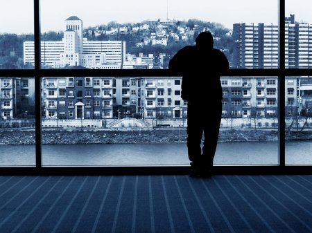 Man waiting - looking out window at city buildings...
