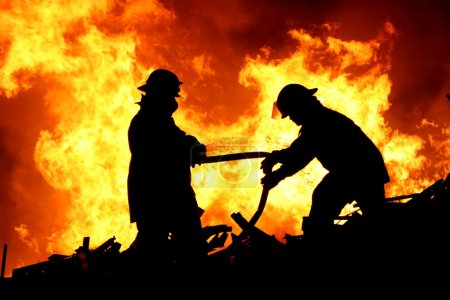 Photo for Silhouette of two firemen fighting a raging fire with huge flames of burning scrap timber - Royalty Free Image
