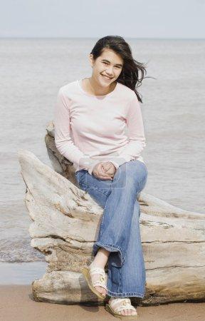 Teen girl sitting on fallen log by lake