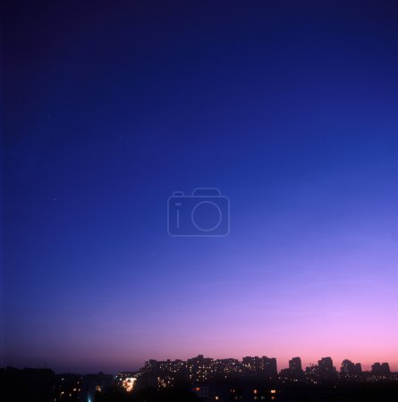 Photo for Twilight over a city with houses silhouettes against the sky. - Royalty Free Image