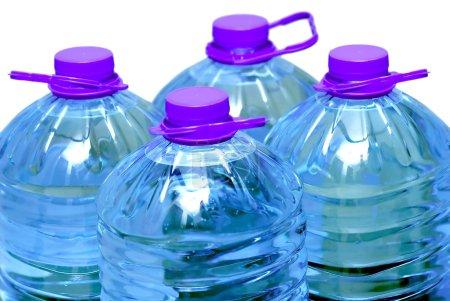 Photo pour Quatre bouteilles d'eau isolé sur fond blanc - image libre de droit