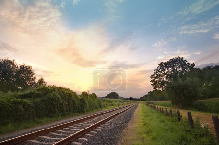 Photo pour Voies ferrées dans une scène rurale avec un beau coucher de soleil pastel - image libre de droit