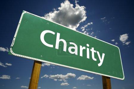 Photo pour Panneau de signalisation de charité avec dramatique ciel bleu et nuages. - image libre de droit