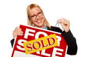 Mujer sosteniendo las llaves vendido por señal de venta