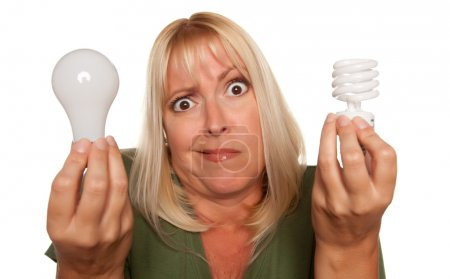 Photo for Funny Faced Woman Holds Energy Saving and Regular Light Bulbs Isolated on a White Background. - Royalty Free Image