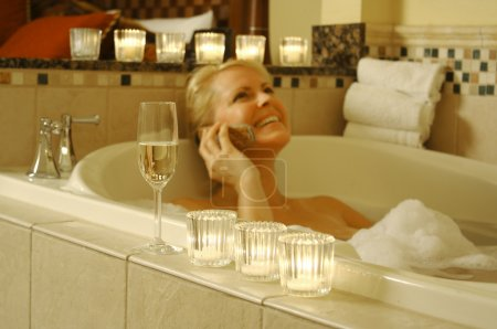 Woman in Bath with Champagne and Phone