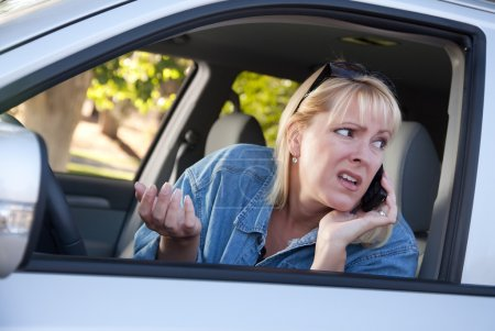 Photo for Concerned Blonde Woman Using Cell Phone While Driving. - Royalty Free Image