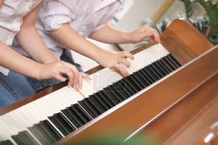 Photo for Brother and Sister Playing the Piano Together - Royalty Free Image