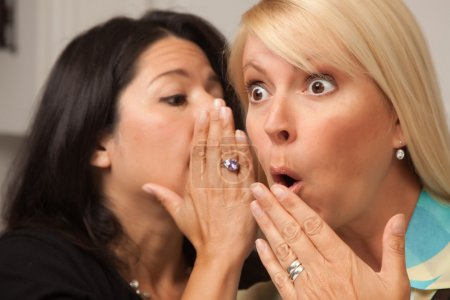 Photo pour Deux amis chuchotant des secrets à l'oreille . - image libre de droit