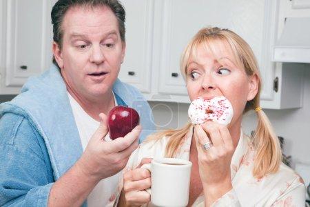 Couple in Kitchen Eating Donut vs Fruit