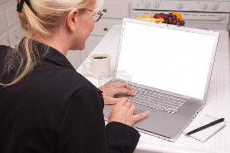 Woman Sitting In Kitchen Using Laptop with Blank Screen