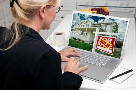 Photo pour Femme dans la cuisine à l'aide d'ordinateur portable à la recherche de biens immobiliers. écran peut être facilement utilisé pour votre propre message ou une image. - image libre de droit