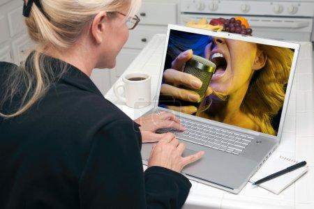 Photo pour Femme dans la cuisine à l'aide d'ordinateur portable pour la musique et du divertissement. écran peut être facilement utilisé pour votre propre message ou une image. - image libre de droit
