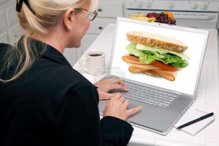 Girl Using Laptop, Sandwich on Screen