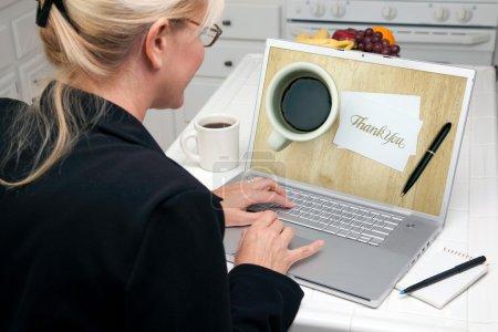 Photo pour Femme dans la cuisine avec ordinateur portable Merci image sur l'écran. écran peut être facilement utilisé pour votre propre message ou une image. image sur écran est mon copyright comme nous - image libre de droit