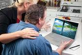 Coppia in cucina utilizzando il computer portatile alla ricerca di viaggio