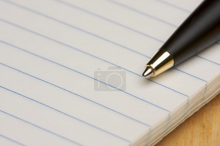 Pen and Pad of Lined Paper on Wood