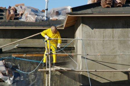 Photo pour La pression des travailleurs de la construction lave la surface fraîche appliquée de l'extérieur de la maison neuve . - image libre de droit