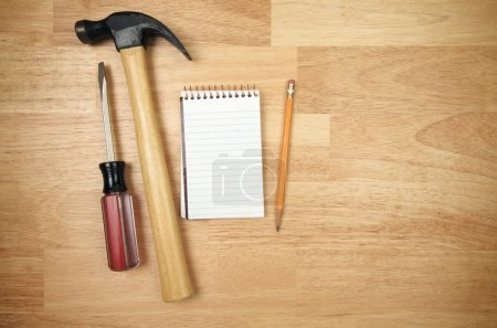 Foto de Bloc de papel, lápiz, martillo y un destornillador sobre un fondo de madera - Imagen libre de derechos
