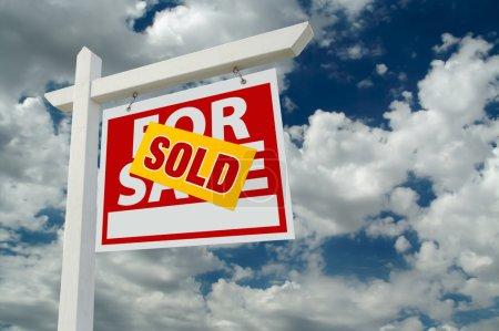 Foto de Vendido por venta inmobiliaria señal en el cielo nublado - Imagen libre de derechos