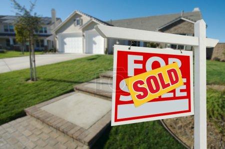 Foto de Casa vendida por señal de venta inmobiliaria en frente de la casa nueva - Imagen libre de derechos