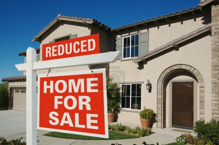 Reduced Home For Sale Sign and New House