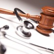 Gavel and Stethoscope on Gradated Background with ...