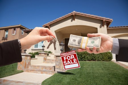 Photo for Handing Over Cash For House Keys in Front of House and Foreclosure Sign. - Royalty Free Image