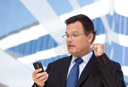 Excited Businessman Using Cell Phone