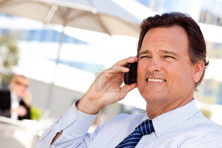 Photo pour Confiant, bel homme d'affaires sourit alors qu'il parle sur son téléphone portable . - image libre de droit
