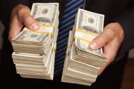 Businessman Holding Stacks of Money