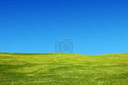 Photo pour Paysage avec des collines herbeuses et un ciel clair - image libre de droit