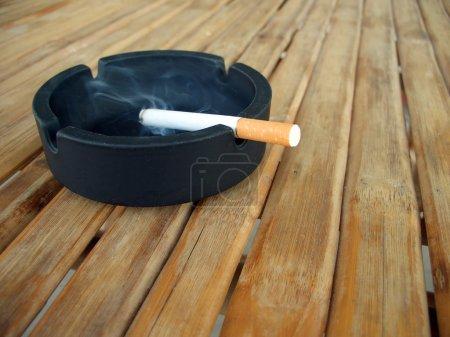 Ashtray with lit cigarette