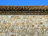 Ancient tiled roof and stone wall